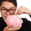 Asian businessman smile put a coin to a pink piggy bank — Stock Photo #57871679