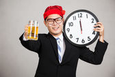 Happy Asian businessman with beer and clock at  midnight — Stock Photo