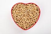Soybeans in heart shape box — Stock Photo