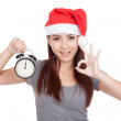 Asian girl with red santa hat show OK with alarm clock — Stock fotografie #60097403