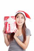 Asian girl with santa hat think what inside a gift box — Stock Photo