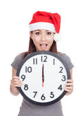 Asian girl wear red christmas hat excited with clock at midnight — Stock Photo
