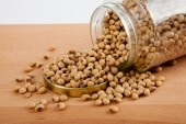 Soybean in a jar with lid off on wood table — Stock Photo