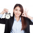 Young Asian businesswoman show OK with alarm clock — Stock Photo #61613569