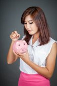 Beautiful Asian girl put a coin to pink pig money box — Stock Photo