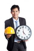 Asian engineer man hold hardhat and a clock — Stock Photo