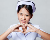 Very happy young Asian nurse show heart hand sign — Stock Photo