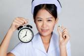 Young Asian nurse with clock and capsule — Stock Photo