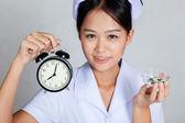 Close up Asian young nurse with clock and pills — Stock Photo
