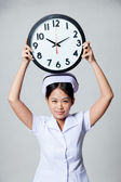 Young Asian nurse show a clock over her head — Stock Photo