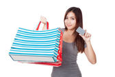 Young Asian woman with shopping bag and blank card — Stock Photo