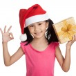 Little asian girl with santa hat and gift box show OK — Stock Photo #73381247