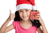 Happy little asian girl show thumbs up with santa hat and gift b — Stock Photo
