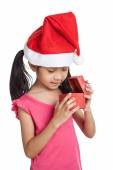 Happy little asian girl with santa hat and gift box — Stock Photo