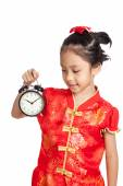 Asian girl in chinese cheongsam dress with a clock — Stock Photo