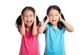 Asian twins girls cover their ears — Stock Photo