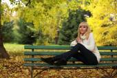 Girl with a cup of coffee on a bench in the park in autumn — Stock Photo