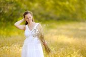 Cute happy girl is on the field, gathering the wheat. — Stock Photo