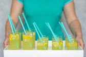 Fresh lemonade with lemon poured into glasses. — Stock Photo