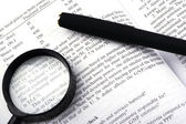 Book, pen and magnifying glass — Stock Photo