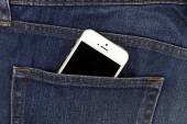 Part of mobile white cellphone in the back pocket of blue denim  — Stock Photo