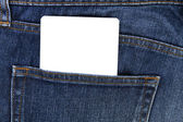 Part of white card paper in the front pocket of blue denim jeans — Stock Photo