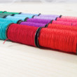 Rainbow of colourful thread spools on the table — Stock fotografie #53396627