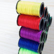 Rainbow of colourful thread spools on the table — Foto de Stock   #53396685