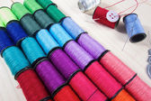 Rainbow of colourful thread spools on the table — Foto Stock