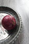 Red onion in silver antique bowl with spec for adding copy — Stock Photo