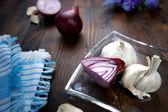 красный лук с чесноком на коричневые деревянные платы и стекла блюдо — Стоковое фото