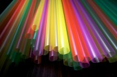 Bright colorful drinking straws on black background — Stock Photo