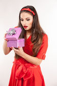 Young attractive brunette woman holding christmas gift. — Stock Photo