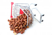 Shopping Cart tilted and filled with Hazel Nuts — Stock Photo