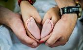Happy family, parents hands with baby feet — Stock Photo