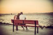 Evening sunset on the beach, couple on the bench — Foto de Stock
