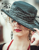Young pretty sexy lady in black vintage hat outdoor — Stock Photo