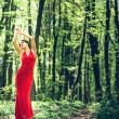Woman in long red dress walking in the forest — Stockfoto #72992161