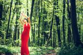 Woman in long red dress walking in the forest — Stockfoto