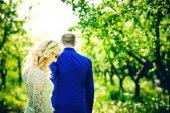 Positive wedding couple outdoor in the garden — Stock Photo