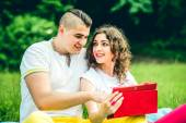 Happy couple relaxing outdoor on the blue sheet — Stock Photo