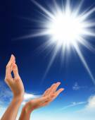Hands, sun and blue sky with copyspace — Stock Photo