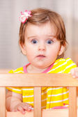 Small child with a hairpin standing in crib. — Stock Photo
