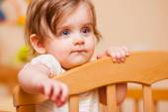Küçük kız yatağına ayakta — Stok fotoğraf