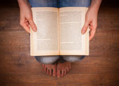 Girl in jeans sitting and reading a book. — Fotografia Stock