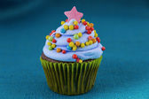Cupcake with blueberry frosting and colorful sprinkles — Stock Photo