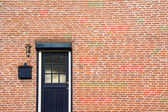 Door on brick wall, side of a house — Stock Photo