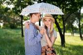 Loving couple standing under an umbrella — Stock Photo