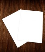 Blank white paper A-4 flyer collection on wooden background — Stock Photo