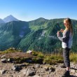 Girl standing on a rock and looking at the valley — Stock Photo #53873403